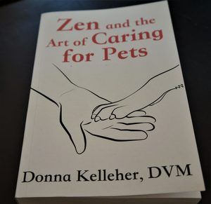 Zen and the art of caring for pets book cover - white paper with red test with black line drawing of a person's hand with a pet's paw in it